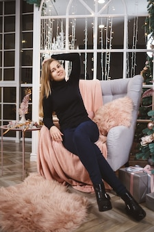 Mooie vrouw in een gebreide trui zit op een fauteuil tegen de achtergrond van een luxueus ingerichte kamer met een kerstboom. goede nieuwjaars geest