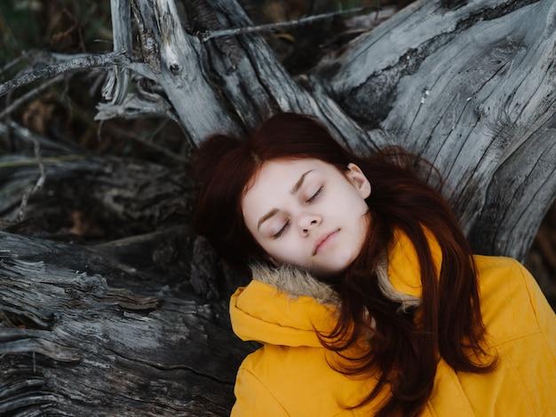 Mooie vrouw in een geel jasje ligt op een boom in de bosrust