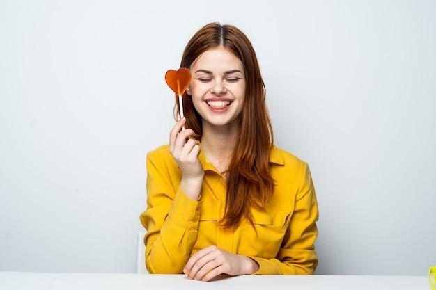 Mooie vrouw in een geel overhemd zit aan een tafel met een hartvormige lolly