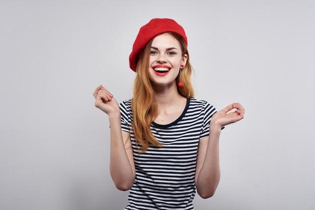 Mooie vrouw in een gestreept t-shirt rode lippen gebaar met zijn handen geïsoleerde achtergrond