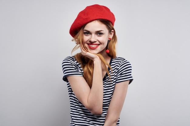 Mooie vrouw in een gestreept t-shirt rode lippen gebaar met zijn handen modelstudio