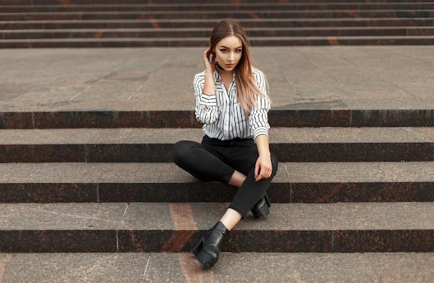 Mooie vrouw in een gestreepte blouse, zwarte jeans en schoenen die op de treden zitten