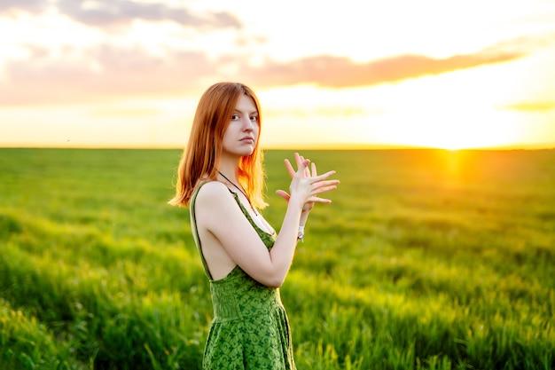 Mooie vrouw in een groene jurk bij weide op zonsondergang