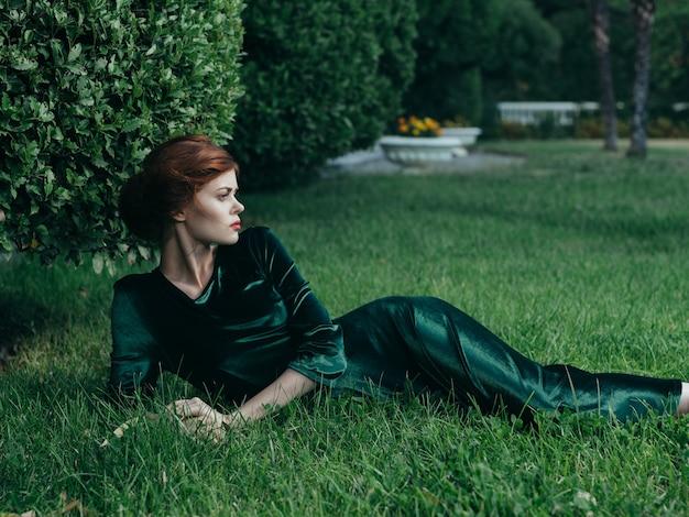 Mooie vrouw in een groene jurk buiten ligt op het gras gotische stijl maskerade charme