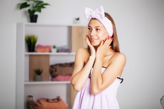 Mooie vrouw in een handdoek jurk met een perfecte huid na home spa-behandelingen