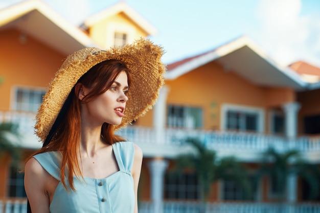Mooie vrouw in een hoed en kleding op een achtergrond van een mooi huis