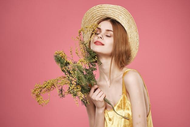 Mooie vrouw in een hoed gouden jurk boeketten bloemen vakantie