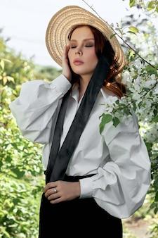 Mooie vrouw in een hoed in het voorjaar in de takken van bloeiende appelstruiken