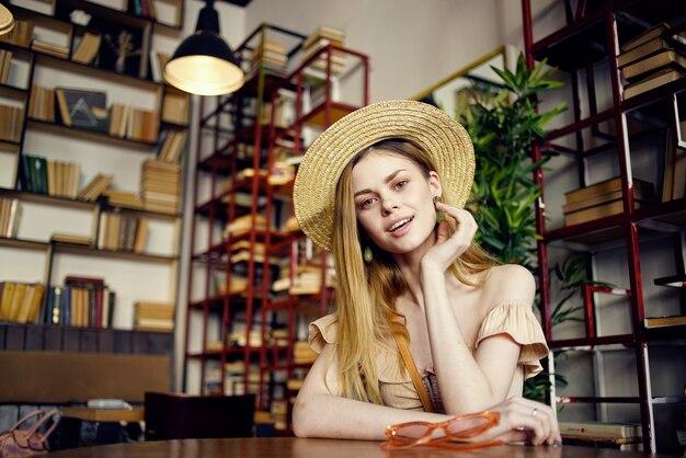 Mooie vrouw in een hoed zittend aan een tafel in een café vakantie boek plezier