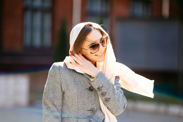 Mooie vrouw in een jas die zich voordeed op straat