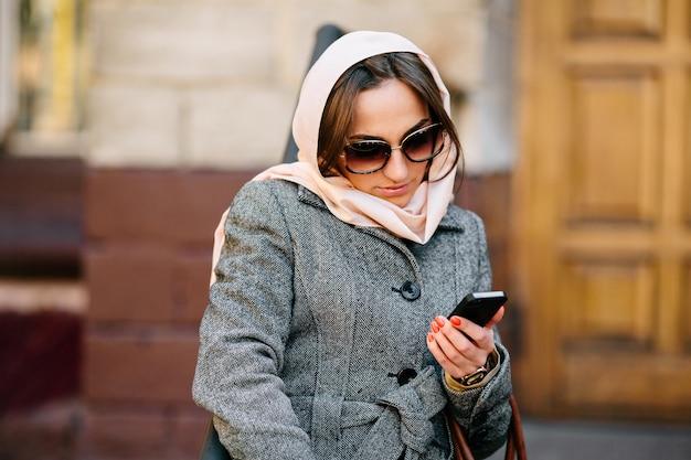 Mooie vrouw in een jas op straat stuurt sms