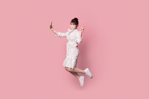 Mooie vrouw in een jurk springen en een selfie maken op een roze studiomuur terwijl ze een medisch masker op het gezicht draagt