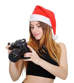 Mooie vrouw in een kerstmuts van de kerstman met een digitale camera