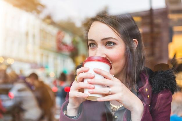 Mooie vrouw in een koffie die een cuf van thee houdt