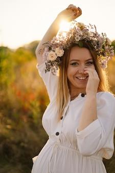 Mooie vrouw in een krans van wilde bloemen die achterover staat in het bloemenveld, handen aan de zijkant