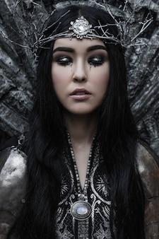 Mooie vrouw in een kroon en harnas