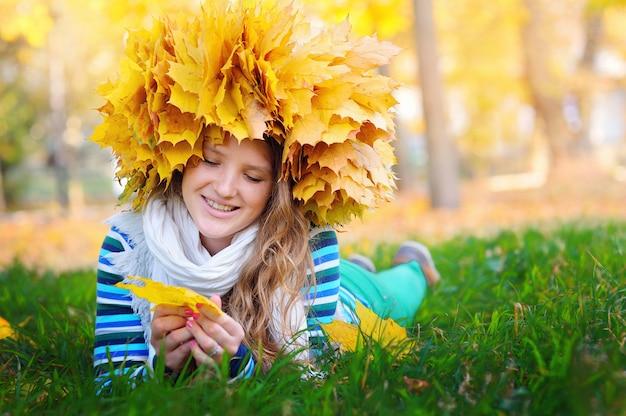 Mooie vrouw in een kroon van gele bladeren die op het gras in de herfstpark liggen