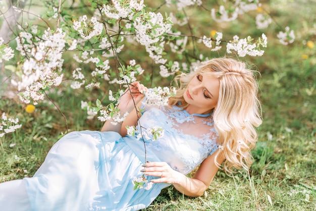 Mooie vrouw in een lange jurk ligt op het gras in een lentetuin