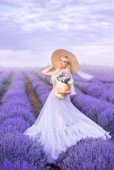 Mooie vrouw in een lange paarse jurk en een grote hoed in lavendel. een meisje met een mand met bloemen in een lavendelveld.