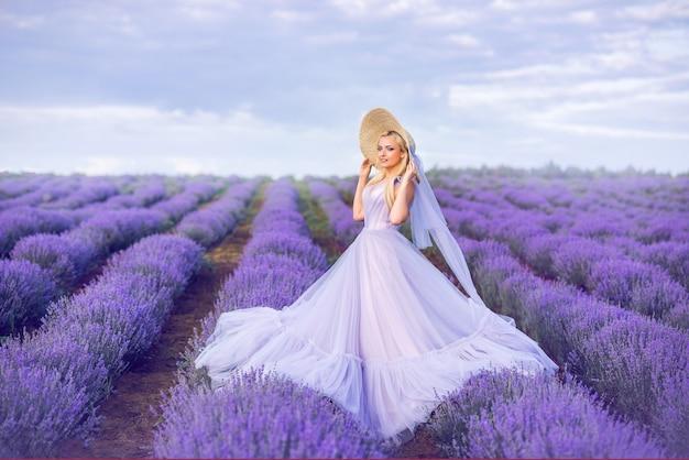 Mooie vrouw in een lange paarse jurk op een achtergrond van lavendel. een meisje in de vorm van een fee en een bloemennimf.