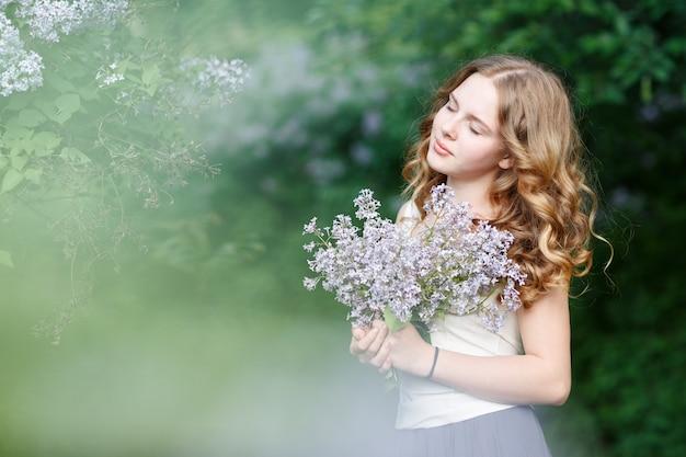 Mooie vrouw in een lichte jurk poseren met bloeiende struiken.