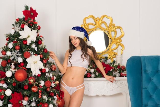 Mooie vrouw in een lingerie in de buurt van kerstmisspar in ingerichte studio