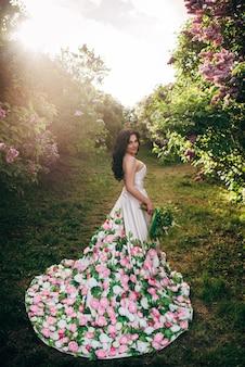 Mooie vrouw in een luxe jurk staat in een bloeiende lila tuin