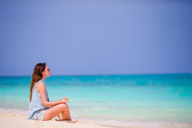 Mooie vrouw in een meditatie op het strand. gelukkig meisje in yogapositie het ontspannen op tropisch strand