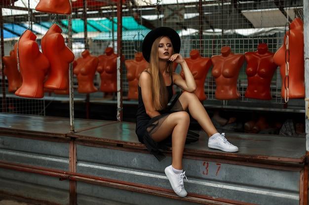 Mooie vrouw in een modieuze zwarte hoed en zwarte rok met witte sneakers zit in de buurt van de mannequins