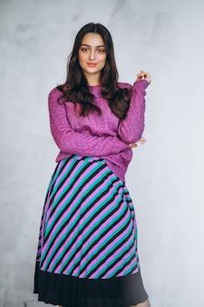 Mooie vrouw in een paarse trui en rok
