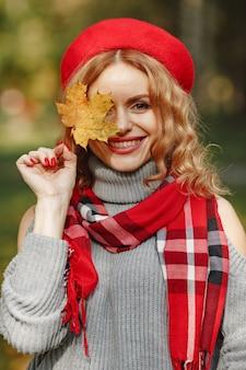 Mooie vrouw in een rode baret houdt herfstblad in de hand.