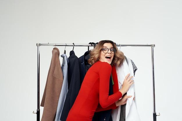 Mooie vrouw in een rode jas in de buurt van de garderobe retail geïsoleerde achtergrond Premium Foto