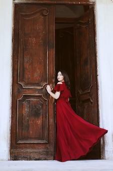 Mooie vrouw in een rode jurk die zich dichtbij een grote houten deur bevindt