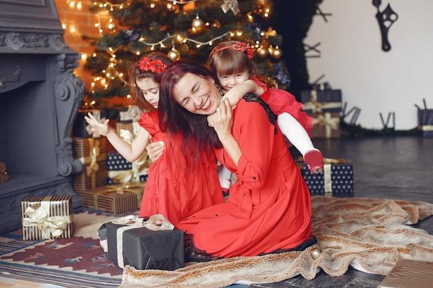 Mooie vrouw in een rode jurk. familie thuis. moeder met dochter.