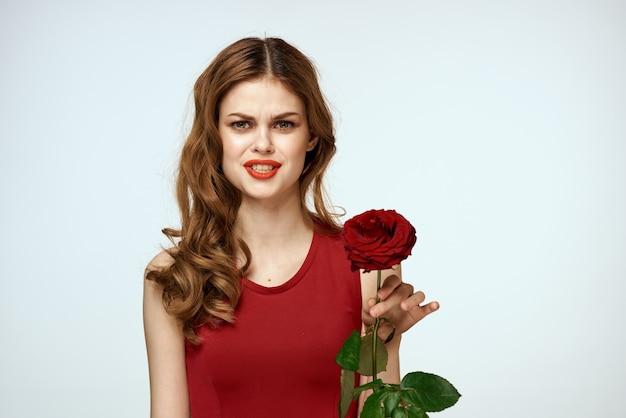 Mooie vrouw in een rode jurk heeft een roos in haar hand een aantrekkelijke uitstraling van cadeau bloemen decoratie.