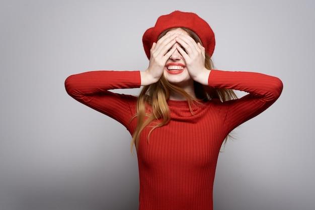 Mooie vrouw in een rode trui cosmetica emotie geïsoleerde achtergrond
