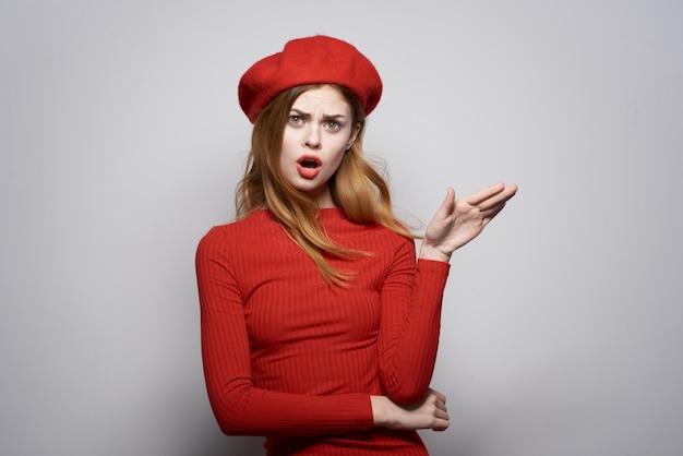 Mooie vrouw in een rode trui cosmetica emotie lichte achtergrond