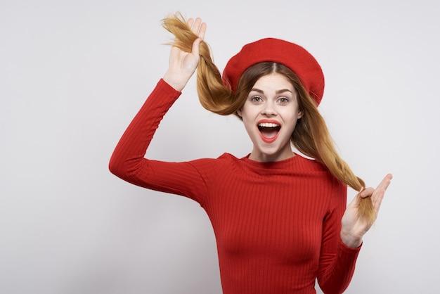 Mooie vrouw in een rode trui cosmetica emotie studio poseren