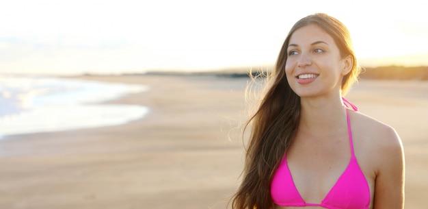 Mooie vrouw in een roze zwembroek op een strand