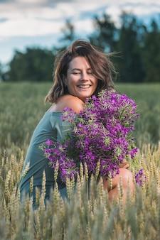 Mooie vrouw in een schattige blauwe jurk en een enorm boeket paarse wilde bloemen lacht en zit op het veld