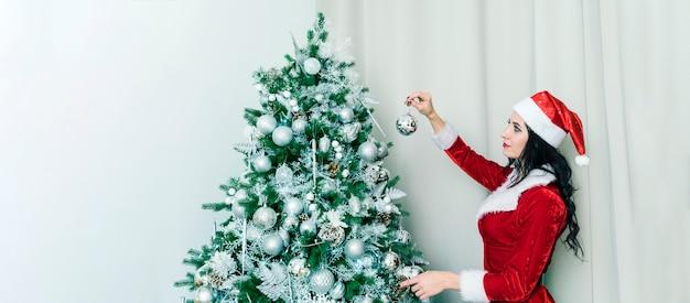 Mooie vrouw in een sexy kostuum van de kerstman versieren de kerstboomversieringen thuis. meisje hangt een zilveren bal aan een groene kerstboom. voorbereidingen voor de nieuwjaarsviering.
