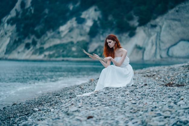 Mooie vrouw in een sprookjesachtige look aan zee, een zachte sprookjesachtige look, witte jurk