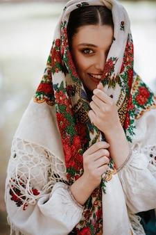 Mooie vrouw in een traditionele etnische jurk met een geborduurde cape op haar hoofd glimlachen