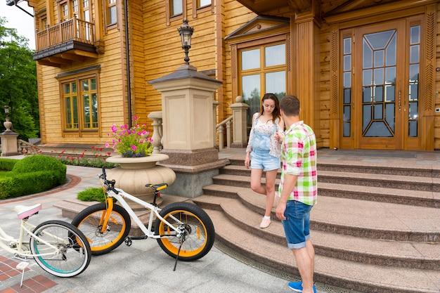 Mooie vrouw in een trendy outfit die op de trap buiten een luxe huis staat en haar man begroet