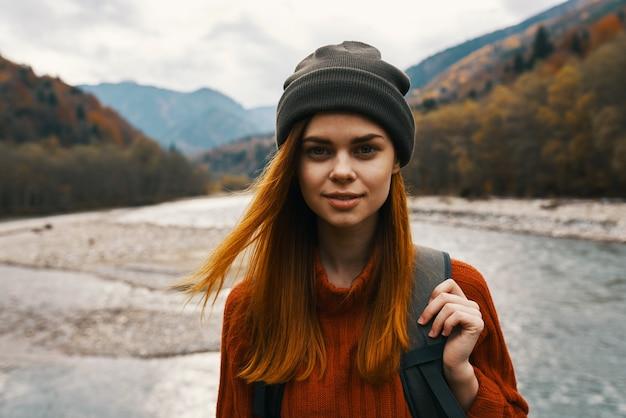 Mooie vrouw in een trui met een rugzak in de bergen in de buurt van de rivier in natuurportret