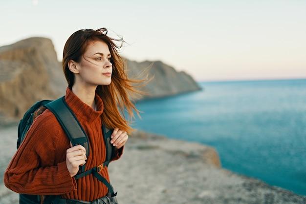 Mooie vrouw in een trui met een rugzak op haar rug in de buurt van de zee in de bergen in de natuur