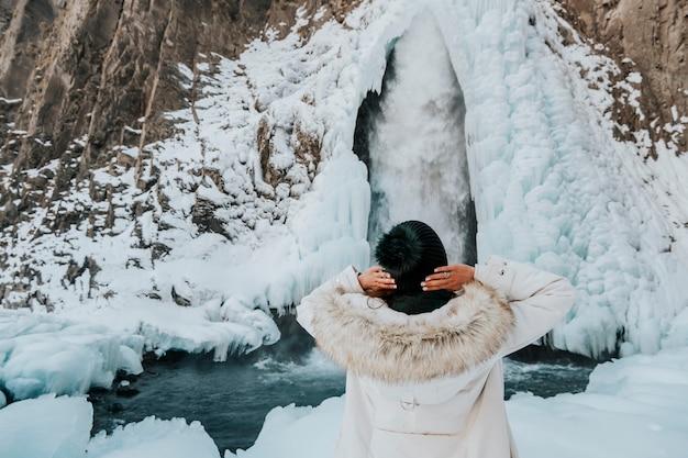 Mooie vrouw in een winterjas tegen de achtergrond van sneeuwwitte bergen.