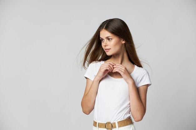 Mooie vrouw in een wit t-shirt houdt haar handen in de buurt van haar gezicht en kijkt naar de zijkant