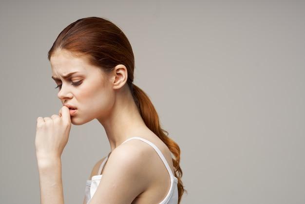 Mooie vrouw in een wit t-shirt op een grijze achtergrond de handen ineen geslagen in de buurt van het gezicht