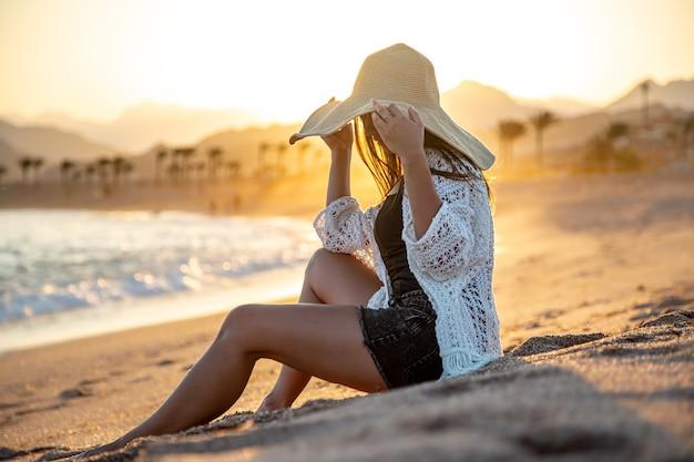 Mooie vrouw in een witte cape met een hoed op haar hoofd die zich voordeed op het strand bij zonsondergang.